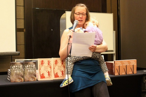 Deb Kalin reading from Cherry Crow Children – all the launch books in the background. Photo by Cat Sparks.